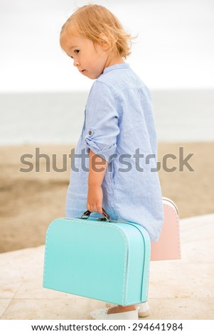 Little girl on vacation at the seaside standing overlooking the beach with her two small suitcases in her hand  side view from behind