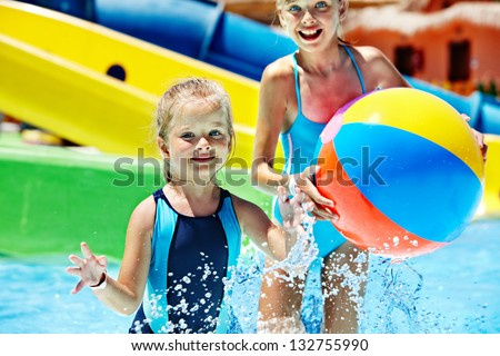 Little girl on water slide at aquapark. - stock photo