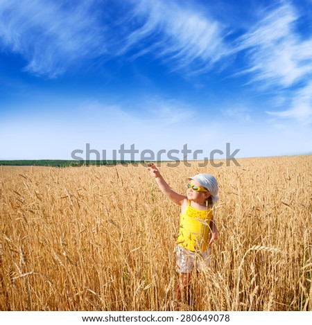 Little girl on wheat field - stock photo