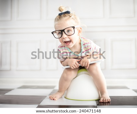 Little girl on white potty with digital tablet  - stock photo