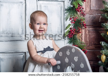 Little girl on wooden horse with christmas background - stock photo