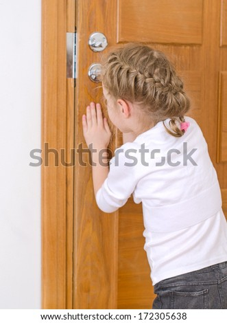 Little girl opening door to someone. - stock photo