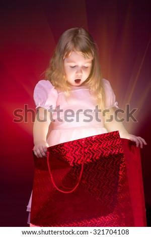 Little girl opening gift packet - stock photo