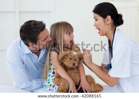 Little girl opening her mouth and the doctor checking her throat during a visit - stock photo