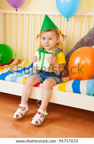 Little girl opening the present sitting on the bed in birthday cap