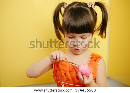 little Girl paint easter eggs in yellow background. Adorable little girl coloring an Easter egg - stock photo