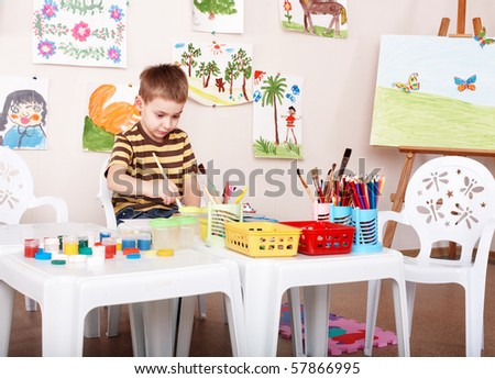 Little girl paint picture in preschool. - stock photo