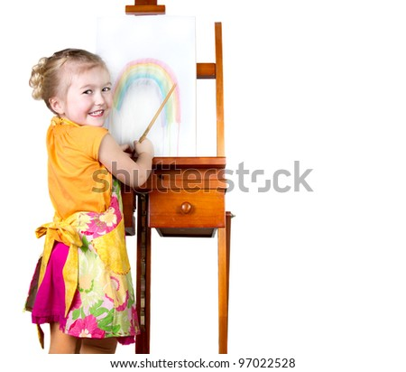 Little girl painting a rainbow on an easel, isolated on white - stock photo