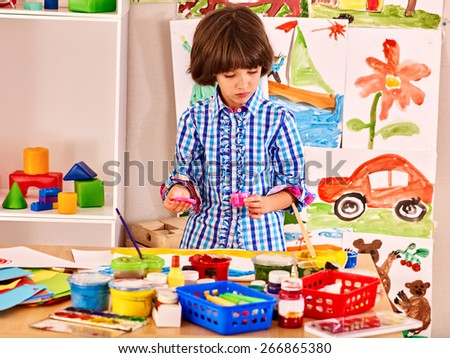 Little girl painting at easel in school. Child painting on background. - stock photo
