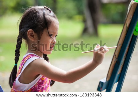 Little girl painting color on easel - stock photo