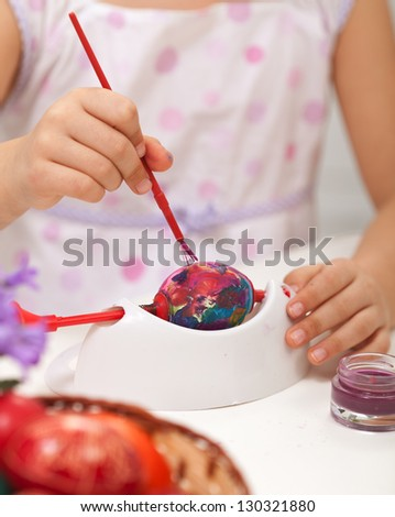 Little girl painting easter eggs with paintbrush - closeup