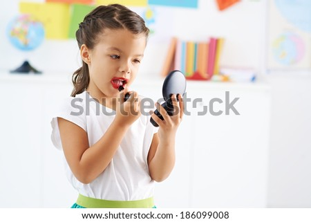 Little girl painting her lips - stock photo