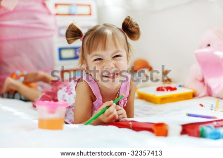 Little girl painting in her nursery at home - stock photo