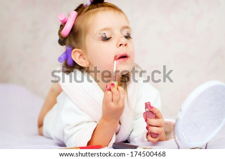 little girl painting lips while wearing hair-rollers and bathrobe - stock photo