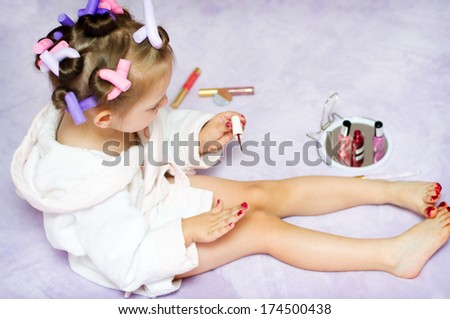 little girl painting nails while wearing hair-rollers, at home - stock photo