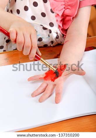 Little Girl Painting On Her Hand at the nursery class - stock photo