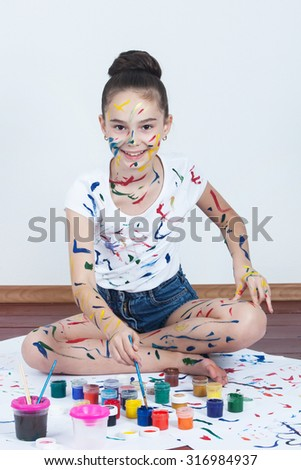 Little girl painting on the walls and floor
