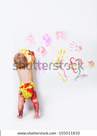 Little girl painting on the walls and floor in studio - stock photo