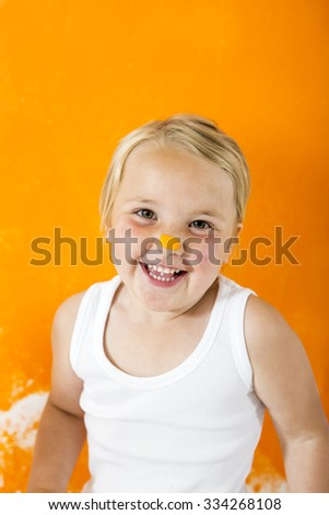 Little girl painting white wall with orange color. She���´s got orange paint on her little nose. - stock photo