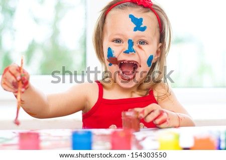 little girl painting with paintbrush and colorful paints - stock photo