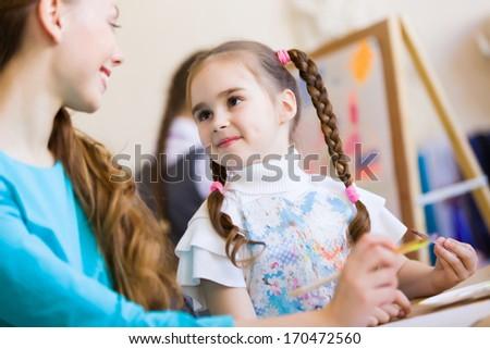 Little girl painting with teacher at kindergarten - stock photo