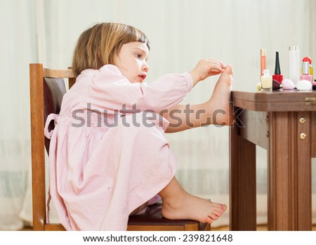 Little girl paints her nails  - stock photo