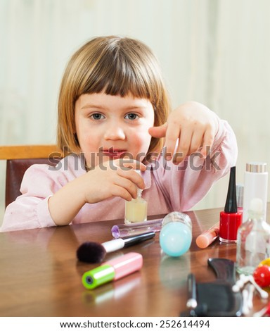 Little girl paints her nails on the hands - stock photo