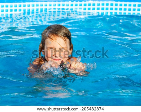 Little girl palying in a swimming pool - stock photo