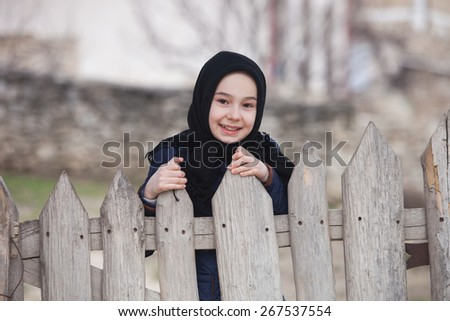 Little Girl Peeking Over an Old Wooden Fence with a Smile While Looking at the Camera. - stock photo