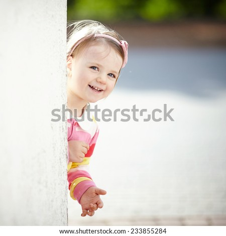 little girl peeping from behind the wall - stock photo