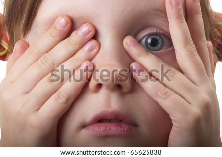 Little girl peeping through hand with one eye macro shot - stock photo