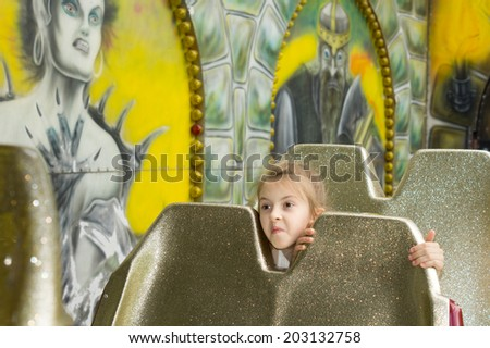 Little girl peering between seats on a ride at a funfair excitedly waiting for the ride to start with a looking of happy anticipation