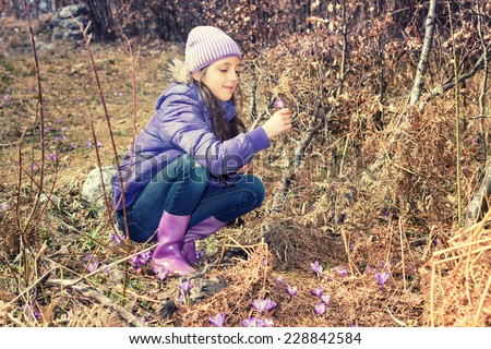 Little Girl picking Crocus in fall forest.Cross processed. - stock photo