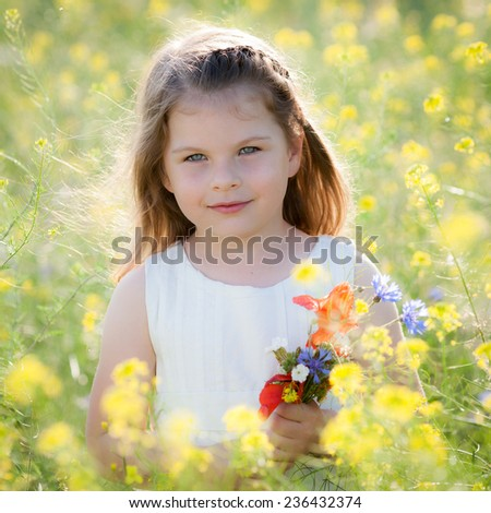 Little girl picking flowers in a meadow - stock photo