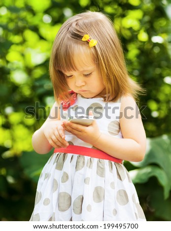 Little girl picking up a mobile phone number