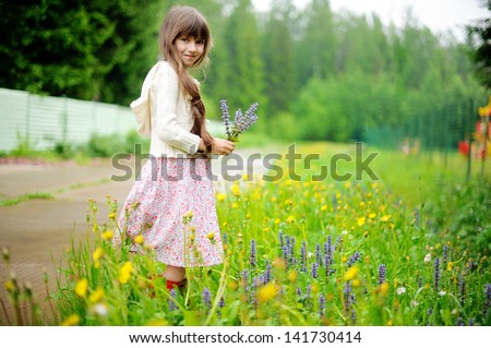 Little girl picking up summer flowers on a meadow - stock photo