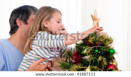 Little girl placing a Christmas star on the top of a tree - stock photo