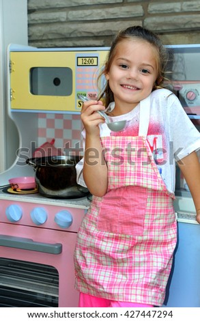 "Little girl ""play acts"" being a mom and cooking for her family.  She is wearing a pink plaid apron and a smile.  She is also holding a spoon tasting her cooking. - stock photo"