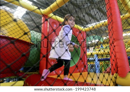 Little girl play in indoor playground. - stock photo