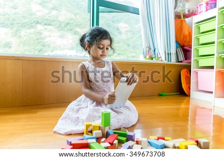 Little girl play tablet pc at her toy room - stock photo