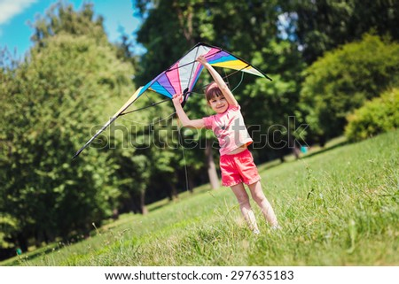 Little girl play with colored kite in the park. Close portrait