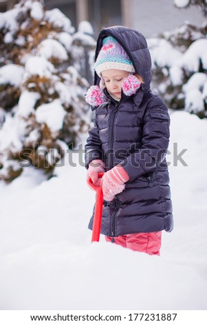 Little girl play with snow shoveling on a winter day