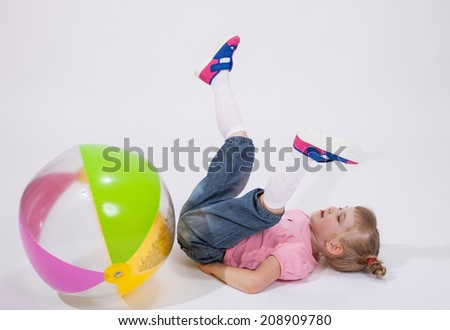 Little girl played with a ball and fell on the floor - stock photo