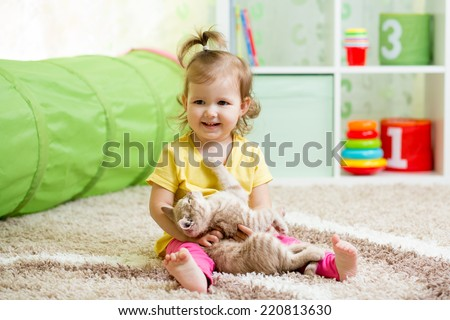 little girl playing and hugging loving pet kitten