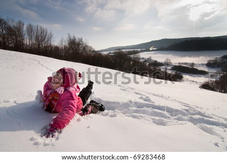 Little girl playing and in the snow - stock photo