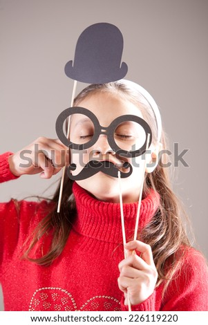 """little girl playing and pretending she's a medician and saying """"Yes of course I am the best more most importan very top doctor of the world"""" with carton moustaches and hat - stock photo"""