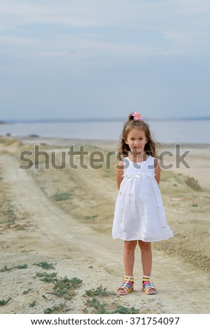 Little girl playing at the summer beach in a white dress