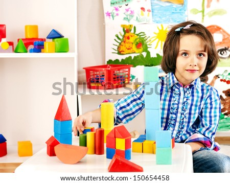 Little girl playing bricks. - stock photo