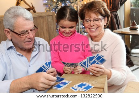 Little girl playing cards with her grandparents - stock photo