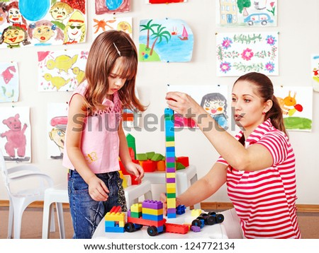 Little girl  playing construction set with mother. - stock photo